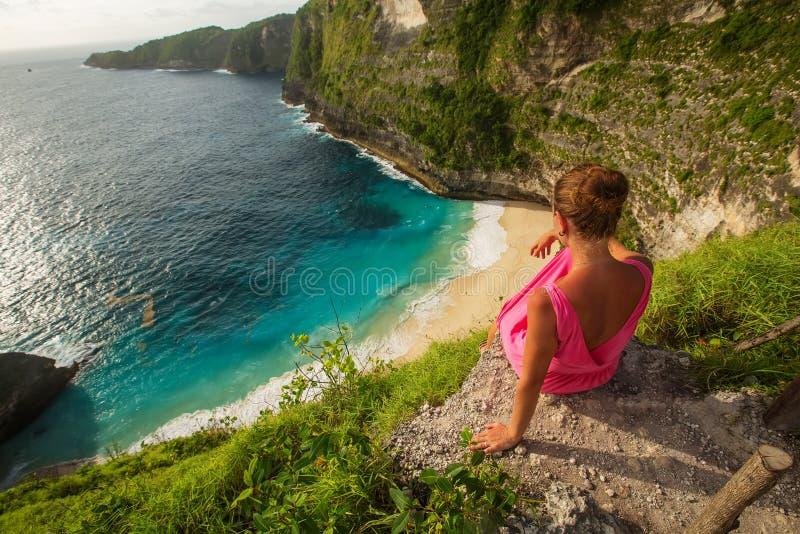 Frau, die am Rand einer Klippe sitzt und Sonnenuntergang, Nusa Penida betrachtet stockfotografie