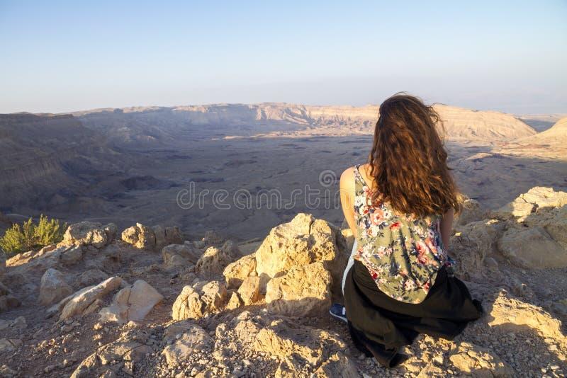 Frau, die am Rand einer Klippe, unten blickend in Richtung des kleinen Kratertales in Israel sitzt stockbild