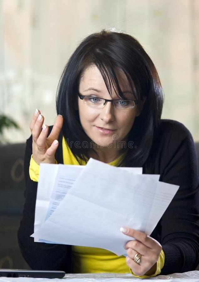 Frau, die Rechnungen überprüft lizenzfreie stockbilder