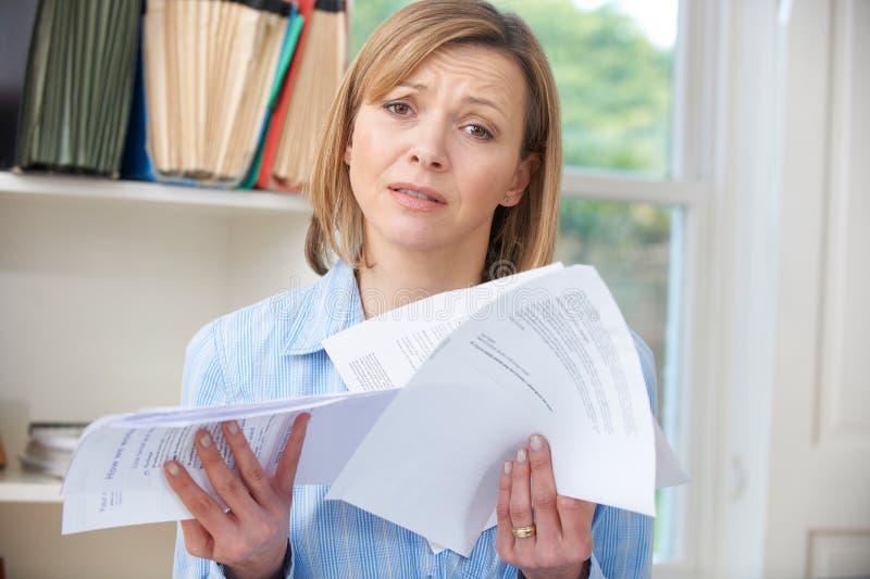 Frau, die Rechnungen betroffen über Schuld hält lizenzfreie stockfotos