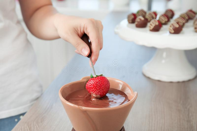 Frau, die reife Erdbeere in Schüssel mit Schokoladenfondue eintaucht lizenzfreies stockfoto