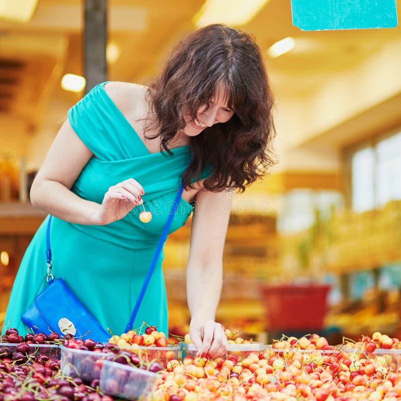 Frau, die reife organische Kirschen auf einem Pariser Markt wählt lizenzfreie stockbilder