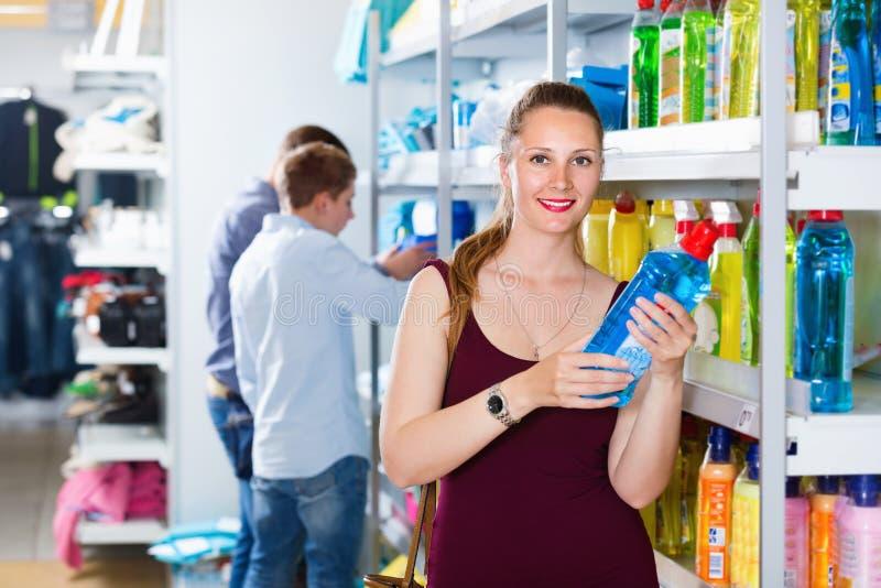 Frau, die Reinigungsmittel an den Waren eines Haushalts im Speicher wählt lizenzfreies stockfoto