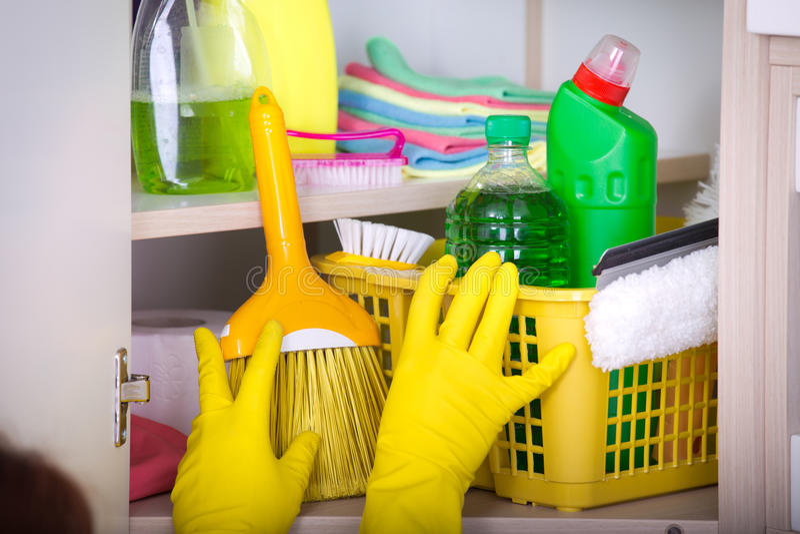 Frau, die Reinigungswerkzeuge im Speiseschrank speichert lizenzfreie stockfotografie