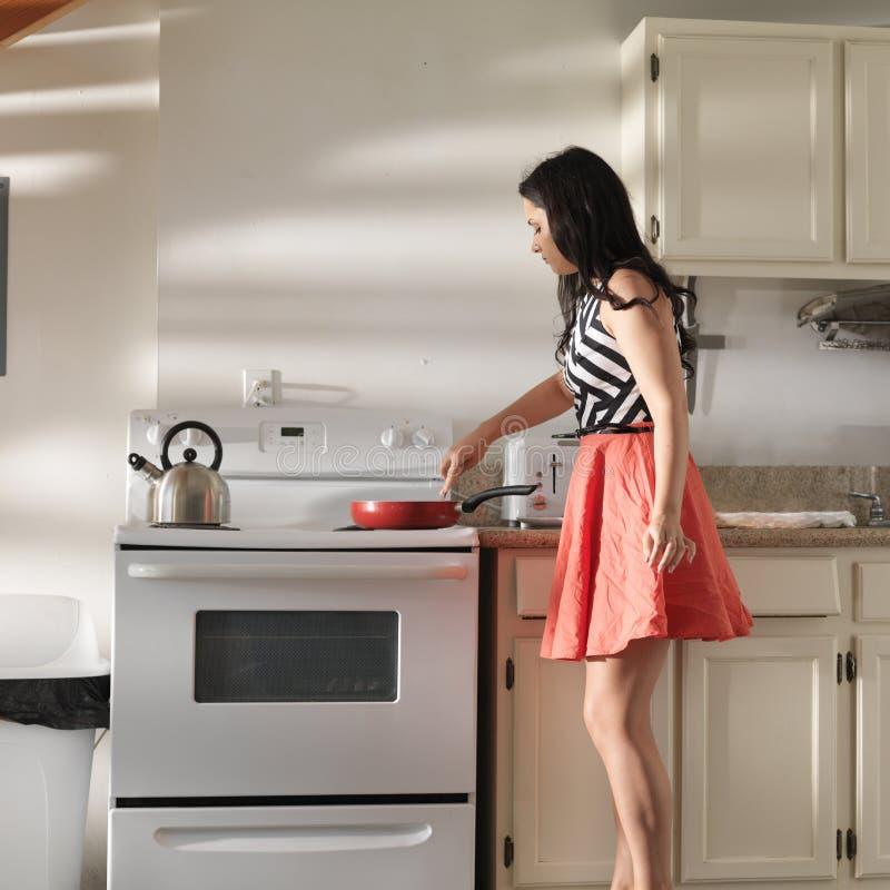 Frau, die Retro- Kleid in der Küche unter Verwendung der Bratpfanne trägt, um zu kochen stockfotos