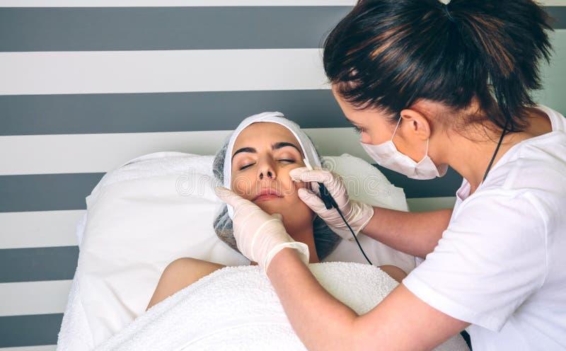 Frau, die Rf anhebt in ihr Gesicht in der Klinik erhält lizenzfreies stockbild