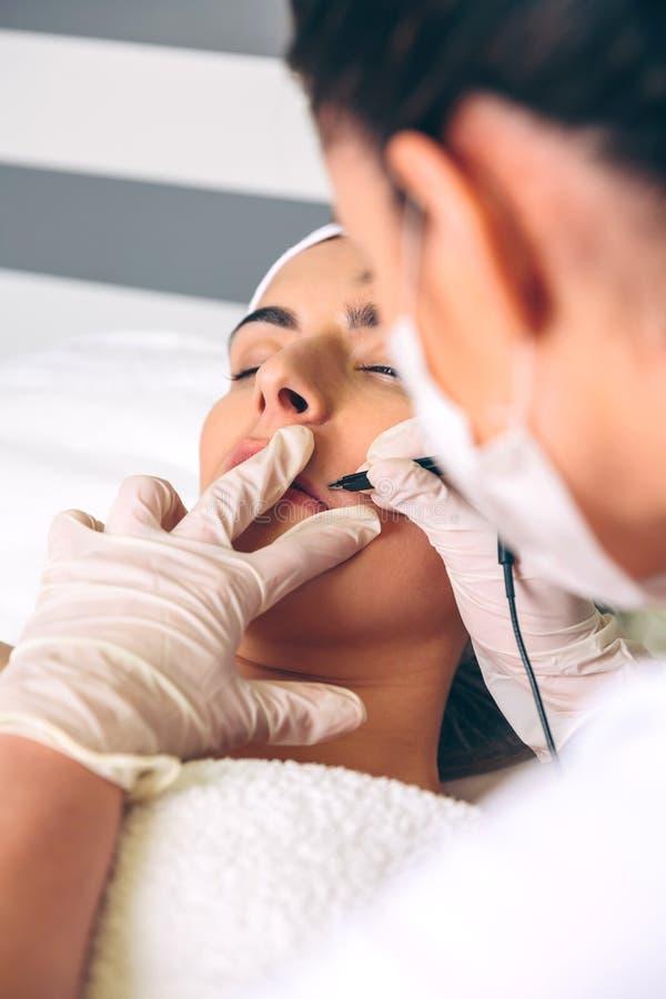 Frau, die Rf anhebt in ihr Gesicht in der Klinik erhält stockfotografie