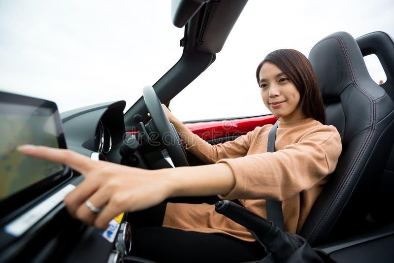 Frau, die Richtung auf Auto GPS-System überprüft lizenzfreie stockbilder