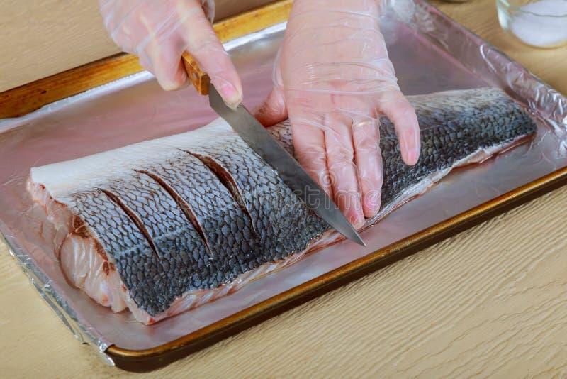 Frau, die rohe Fische auf Küche kocht stockfotografie