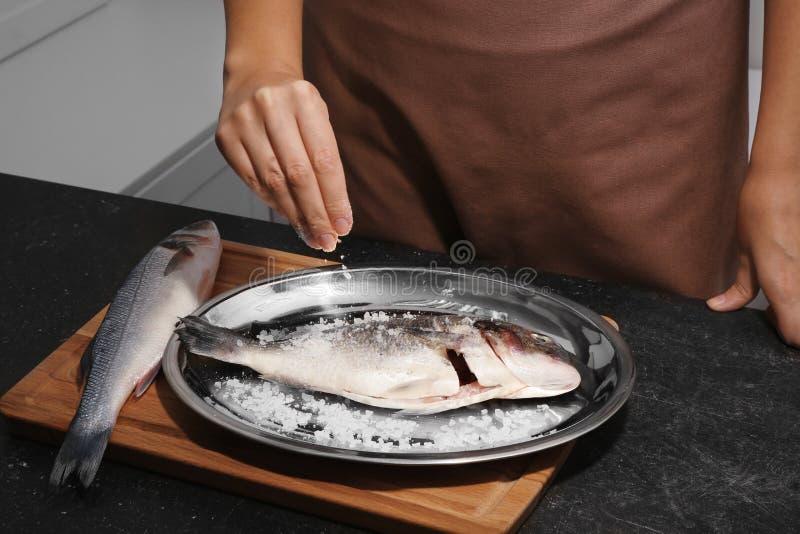 Frau, die rohe Fische kocht lizenzfreie stockfotos
