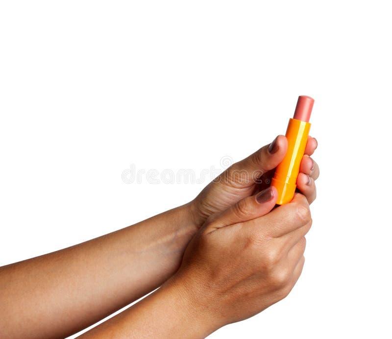 Frau, die rosa Lippenstift in ihrer Hand hält lizenzfreie stockfotografie