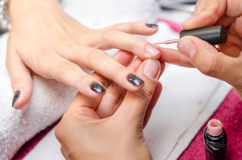 Frau, die rosafarbenen Nagellack anwendet lizenzfreies stockfoto