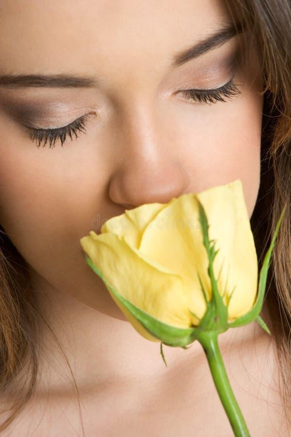 Frau, die Rose riecht lizenzfreie stockbilder