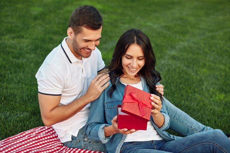 Frau, die rote Geschenkbox zusammen mit Freund öffnet lizenzfreies stockbild