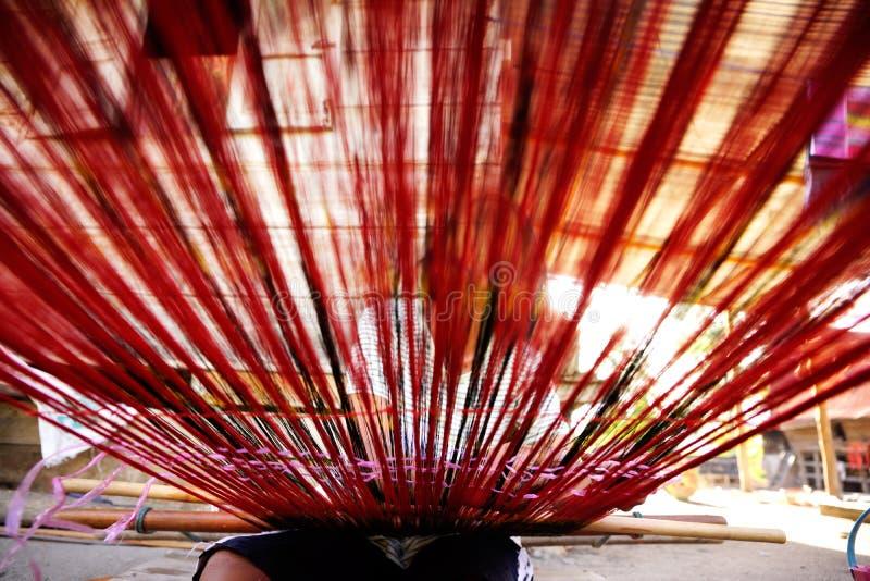 Frau, die rote Threads mit den Händen auf dem spinnenden Gerät gesehen von einer niedrigen Winkelsicht spinnt stockbild