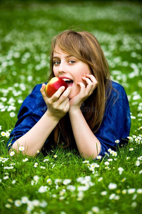 Frau, die roten Apfel isst stockbild