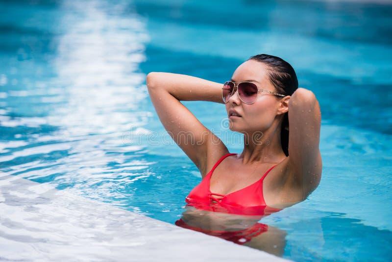 Frau, die roten Badeanzug und die Sonnenbrille sitzt im Swimmingpool, rührendes nasses Haar trägt stockbilder