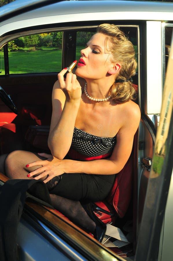 Frau, die roten Lippenstift anwendet stockfotos