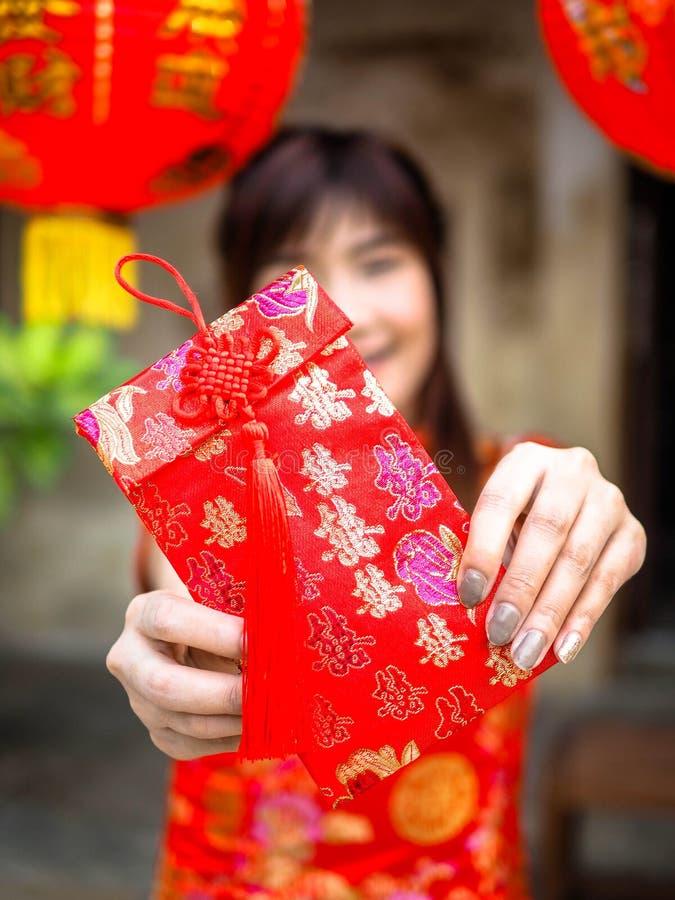 Frau, die roten Umschlag hält, um im Festival des Chinesischen Neujahrsfests zu geben Chinesisches neues Jahr stockfotos