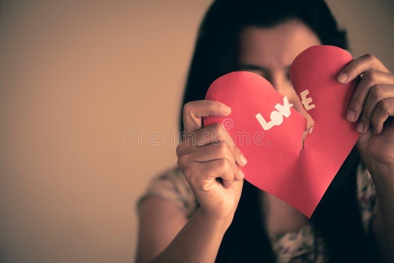 Frau, die rotes defektes Herz mit Liebestext hält stockbilder