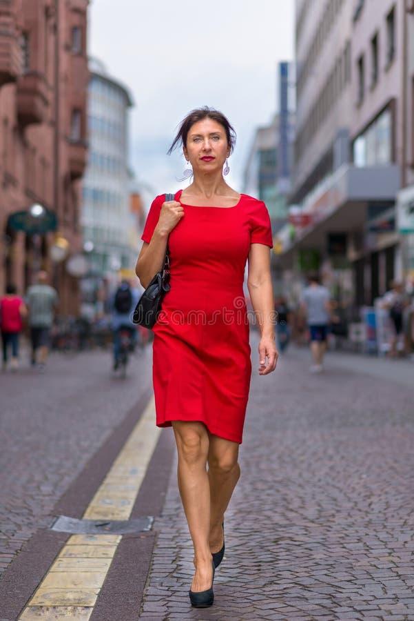 Frau, die rotes Kleid trägt und entlang Straße geht lizenzfreies stockfoto