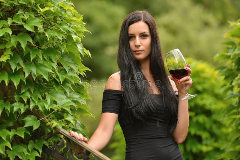 Frau, die Rotwein trinkt lizenzfreie stockfotos