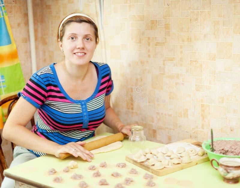 Frau, die russische Mehlklöße (pelmeni, macht) stockfotos