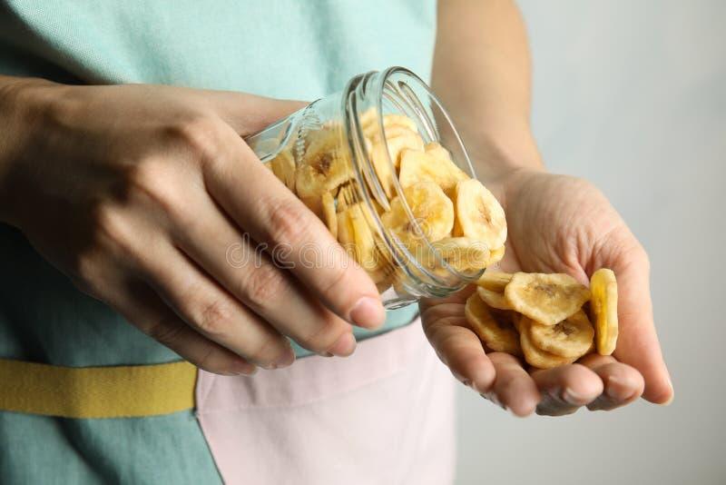 Frau, die süße Bananenscheiben vom Glas gießt, um auf hellem Hintergrund, Nahaufnahme zu übergeben lizenzfreies stockfoto