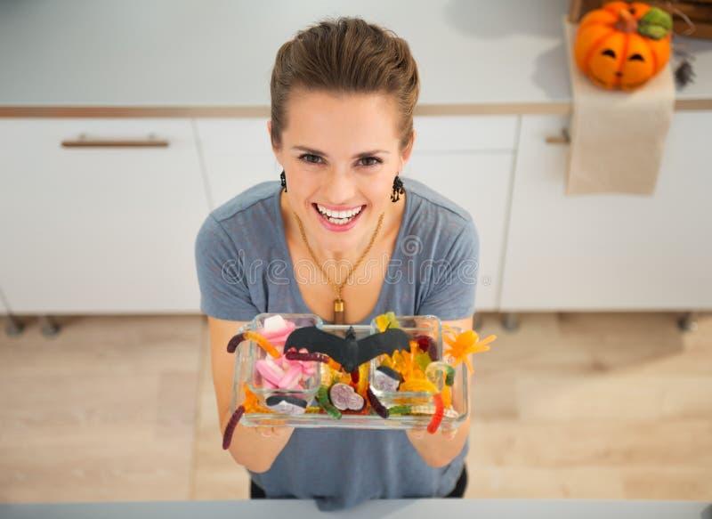 Frau, die Süßes sonst gibt's Saures Teller mit Süßigkeit für Halloween-Partei zeigt lizenzfreie stockbilder