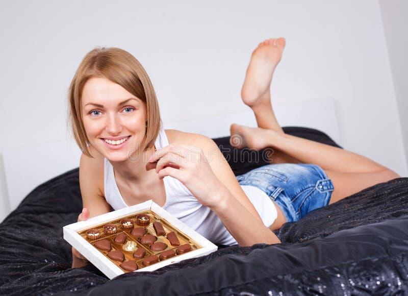 Frau, die Süßigkeiten isst stockfotos