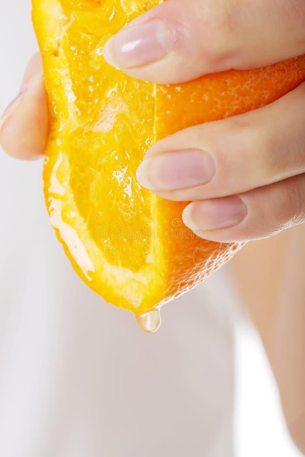 Frau, die Saft von einer Orange zusammendrückt lizenzfreies stockfoto