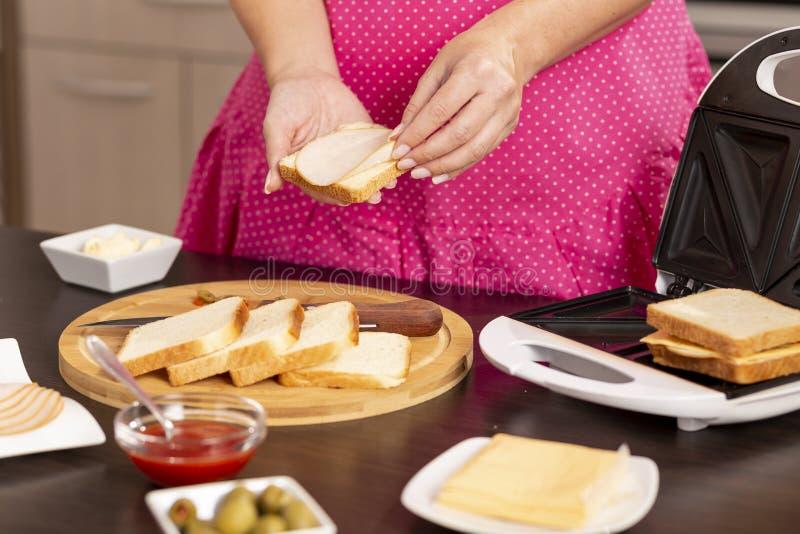 Frau, die Salami auf einem Sandwich hinzufügt stockbilder