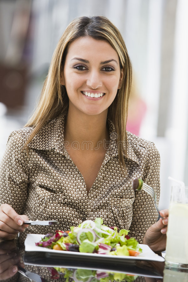 Frau, die Salat am Kaffee isst stockfotos