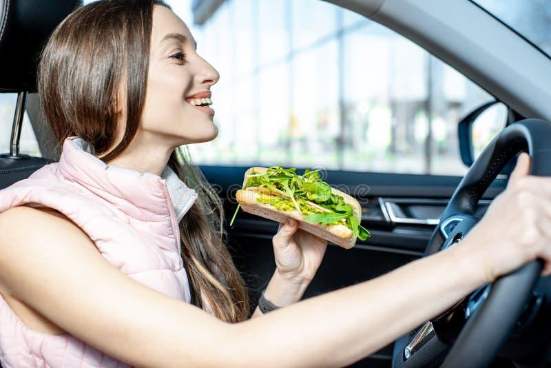 Frau, die Sandwich im Auto isst lizenzfreie stockfotos