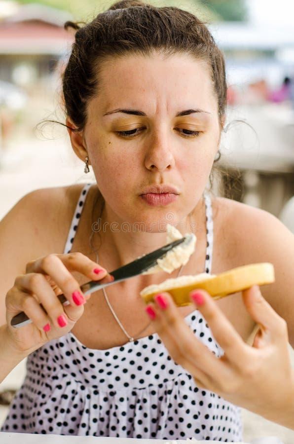 Frau, die Sandwich macht stockfotografie