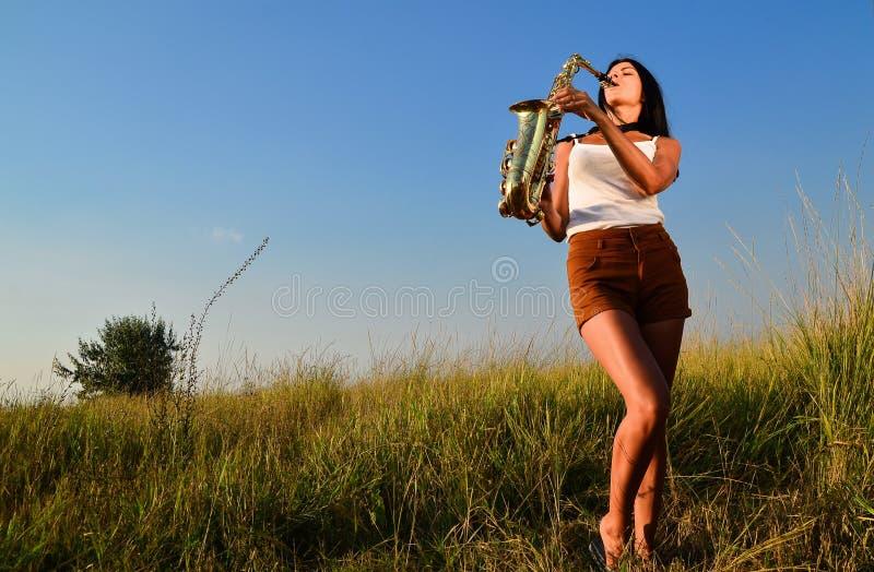 Frau, die Saxophon in der Natur spielt stockbild