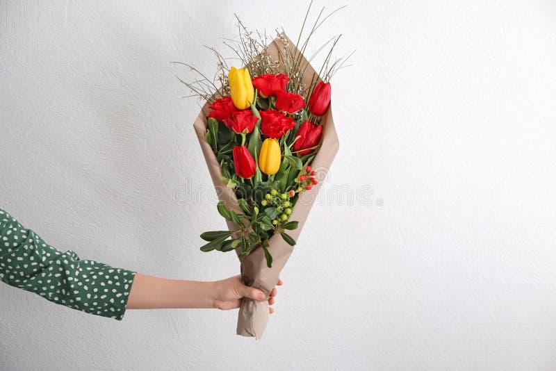 Frau, die schöne Blumen als Geschenk auf hellem Hintergrund hält lizenzfreie stockfotos
