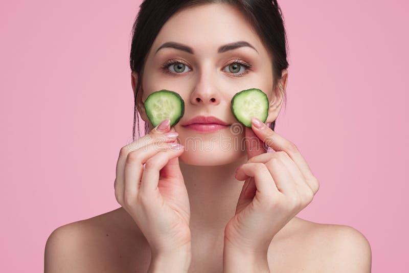 Frau, die Scheiben von Gurken auf Gesicht hält lizenzfreie stockfotografie