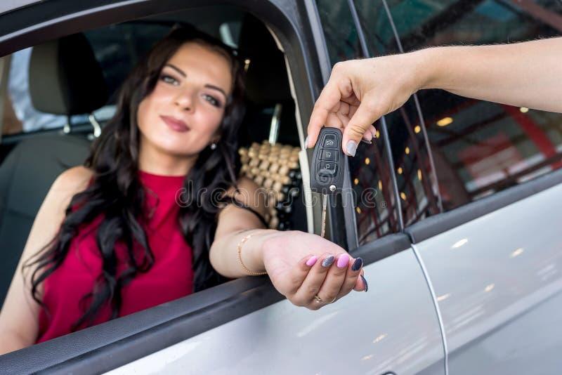 Frau, die Schlüssel von einem Neuwagen empfängt stockfotografie