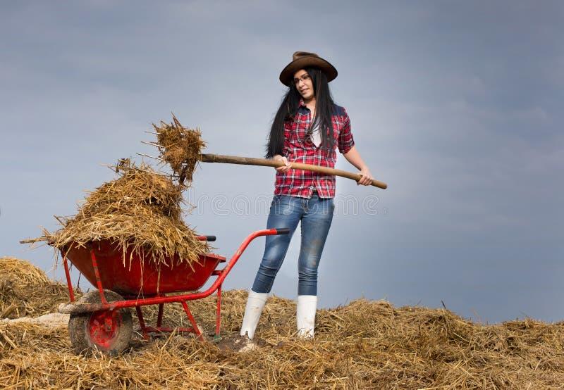 Frau, die schmutzige Arbeiten über Bauernhof bearbeitet lizenzfreie stockfotos