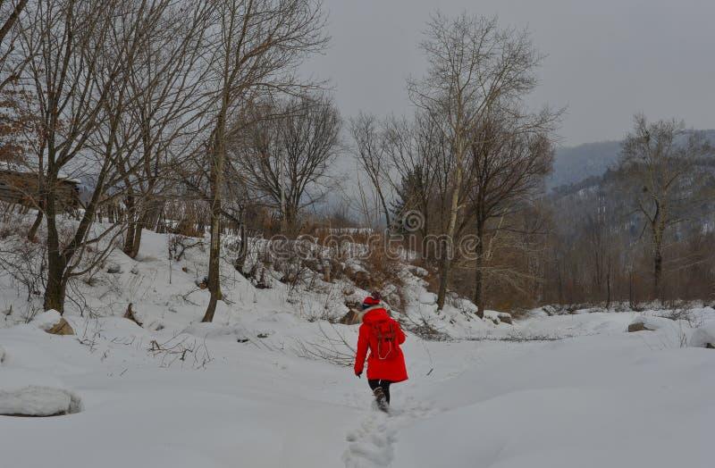 Frau, die am Schneedorf in China geht stockfotografie