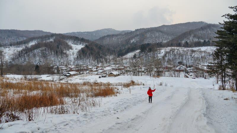Frau, die am Schneedorf in China geht stockbilder
