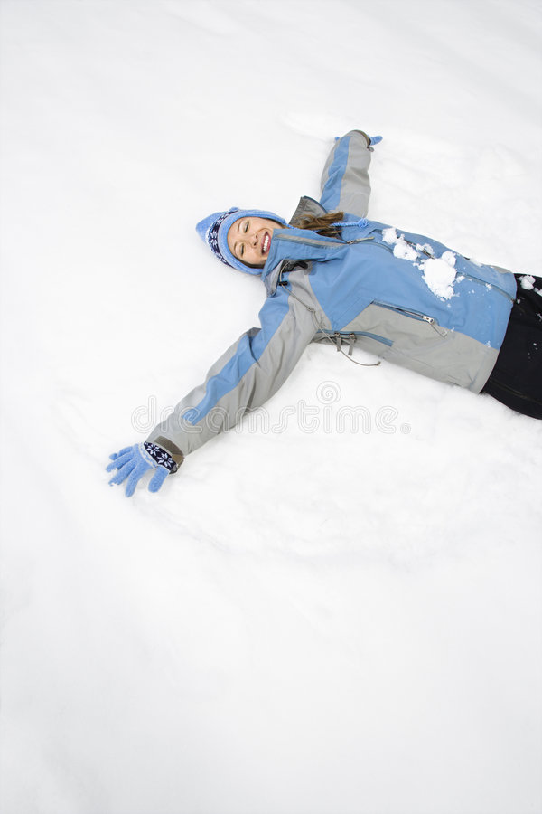 Frau, die Schneengel bildet. lizenzfreie stockfotos