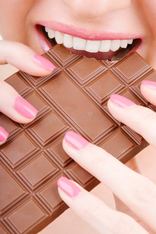 Frau, die Schokolade isst stockfoto