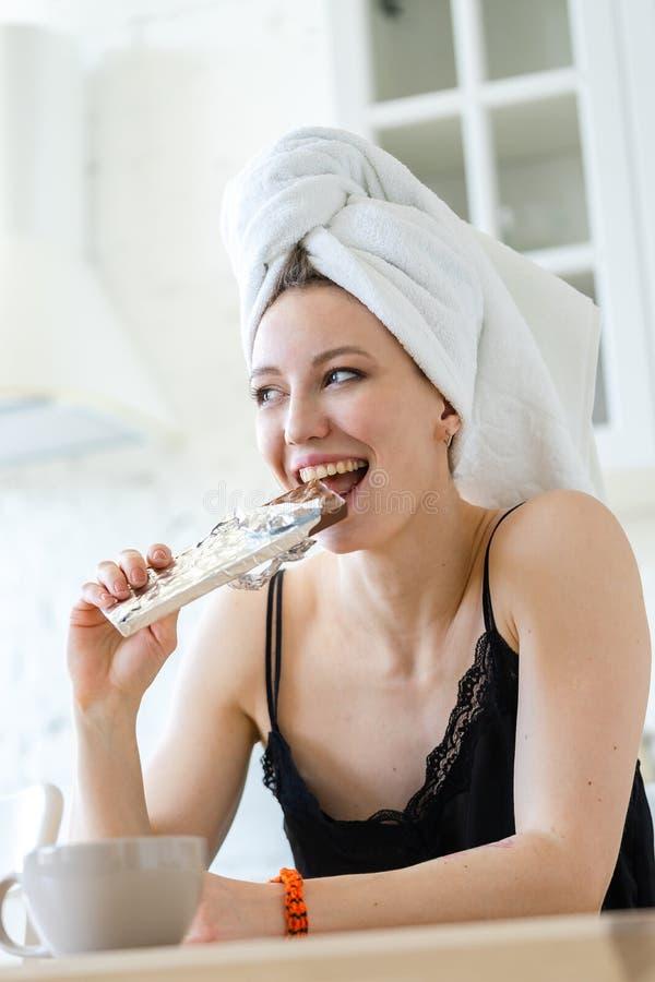 Frau, die Schokolade isst und nachdem Diät genießt, gehalten worden ist Betr?germahlzeit lizenzfreies stockbild