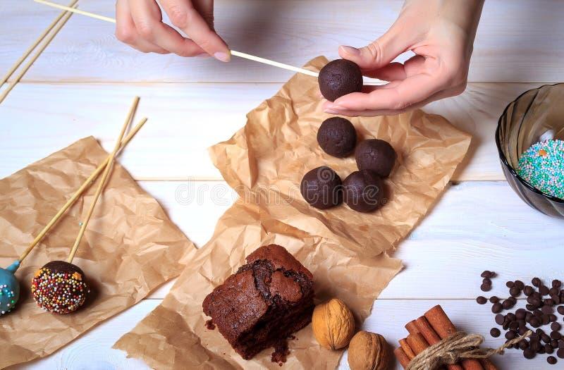 Frau, die Schokolade popcakes macht Kuchen knallt die Herstellung Knall-Kuchen lizenzfreies stockbild