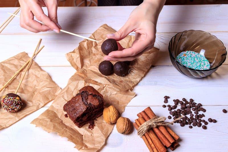 Frau, die Schokolade popcakes macht Kuchen knallt die Herstellung Knall-Kuchen lizenzfreie stockfotos
