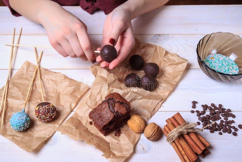 Frau, die Schokolade popcakes macht Kuchen knallt die Herstellung Knall-Kuchen stockbild