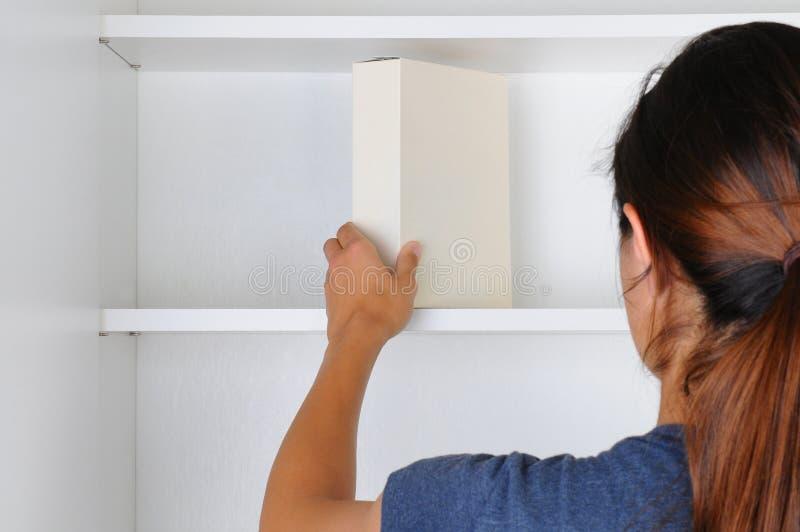 Frau, die in Schrank erreicht stockbild