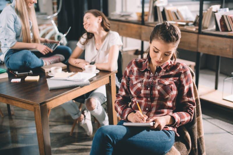 Frau, die in Schreibheft studiert und schreibt lizenzfreie stockfotos